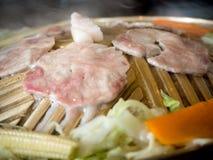 Du porc et des légumes sont placés sur une casserole en laiton Image libre de droits