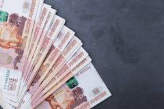 Du?a sterta Rosyjscy pieni?dzy banknoty pi?? tysi?cy rubli k?ama na popielatym cementowym tle obrazy stock