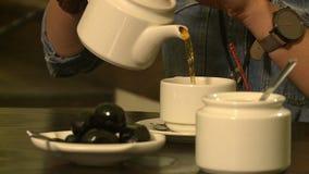 Du thé est plu à torrents dans une cuvette clips vidéos