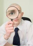 duży facet patrzeje magnifier Obrazy Stock
