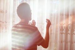 dua悔悟祈祷的回教人室内在光束窗口 免版税图库摄影