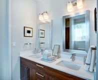 Dual Bathroom Vanity and Mirrors. Bathroom sinks and mirrors for two individuals with stained wood cabinetry royalty free stock photography