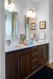 Dual Bathroom Vanity and Mirrors. Bathroom sinks and mirrors for two individuals with stained wood cabinetry stock image