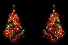 Dual Christmas Trees. On black background with starburst lighting effect Stock Images