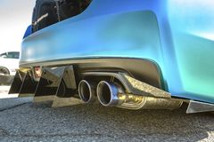 Dual exhaust pipes on a custom car with rear spikes and teal pai. Nt. Custom cars in Southern California summer 2017 Stock Photography