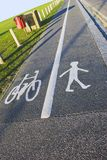 Dual Lane - Cyclists and Pedestrians. A British pavement, divided and signed for cyclists and pedestrians between an open field and a road.  Sunny day, blue sky Royalty Free Stock Image