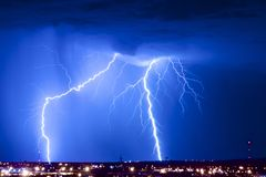 Dual Lightning Strikes. Are captured over an urban scene during a summer monsoon thunderstorm Royalty Free Stock Photos