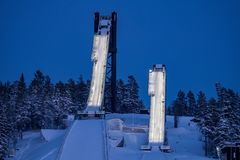 The dual ski jumping slopes or towers in Falun, Sweden. The two ski jumping slopes or towers at Lugnet stadium in Falun, Sweden. Both illuminated in the evening stock photo