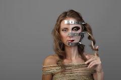 Dualism. Pretty young woman with long wavy hair, with pale angry makeup and iron mask on half of face wrapped in a rough rope on dark gray background - prisoner Royalty Free Stock Photo