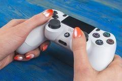 Dualshock Sony PlayStations 4 Gamecontroller in der Gamershand auf hölzerner Hintergrundatelieraufnahme Spielkonsole mit einem St Lizenzfreie Stockfotos