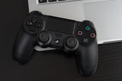 DualShock 4. UFA, RUSSIA - 26 JUNE, 2016: The new Sony Dualshock 4 with MacBook Pro Retina. Sony PlayStation 4 game console of the eighth generation stock photos