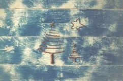 Duas árvores e estrelas de Natal feitas das varas secas em de madeira, azul Fotografia de Stock Royalty Free