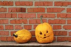 Duas abóboras, lanterna do ` de Jack O contra a parede de tijolo alaranjada do grunge Símbolo do feriado do outono de Dia das Bru Imagem de Stock