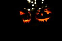 Duas abóboras de Dia das Bruxas com bokeh iluminam-se no fundo preto Fotografia de Stock Royalty Free