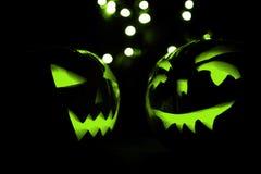 Duas abóboras de Dia das Bruxas com bokeh verde iluminam-se no fundo preto Imagem de Stock
