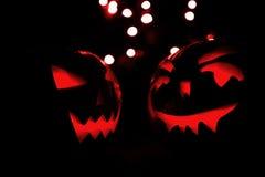 Duas abóboras de Dia das Bruxas com bokeh vermelho iluminam-se no fundo preto Imagens de Stock