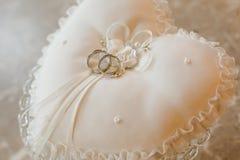 Duas alianças de casamento da prata e do ouro em um coxim Fotografia de Stock