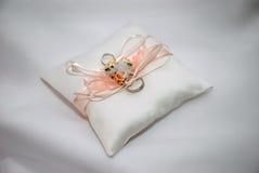 Duas alianças de casamento do ouro branco na almofada branca do laço Imagens de Stock