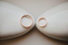 Duas alianças de casamento do ouro que colocam em nupcial branco Fotos de Stock