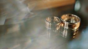 Duas alianças de casamento do ouro que encontram-se nas decorações de um whit da tabela que brilham com fim claro acima do macro  video estoque