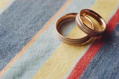 Duas alianças de casamento do ouro que encontram-se no pano colorido Imagens de Stock Royalty Free