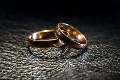 Duas alianças de casamento dos tamanhos diferentes feitos no ouro no couro preto fotos de stock royalty free