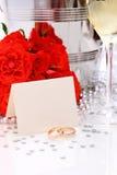 Duas alianças de casamento douradas com cartão, vidros do champanhe Foto de Stock Royalty Free