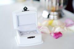 Duas alianças de casamento douradas na caixa branca pequena Fotos de Stock Royalty Free
