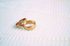 Duas alianças de casamento douradas no fundo claro da fita Fotografia de Stock Royalty Free