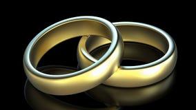 Duas alianças de casamento douradas no fundo preto fotos de stock