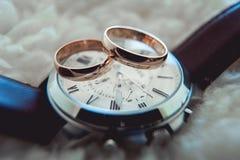 Duas alianças de casamento douradas no relógio com correia marrom Imagem de Stock Royalty Free