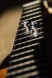 Duas alianças de casamento encontram-se nas cordas de uma guitarra Fotos de Stock Royalty Free