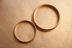 Duas alianças de casamento no fundo amarelo de couro Fotografia de Stock Royalty Free