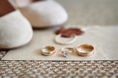 Duas alianças de casamento do ouro e sapatas da noiva no fundo Imagens de Stock