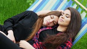 Duas amigas abraçam e dormindo na rede no jardim Pares lésbicas, conceito do lgbt video estoque