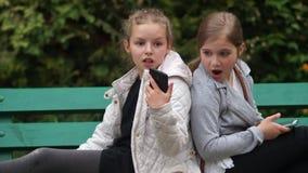 Duas amigas adolescentes estão sentando-se em um banco de parque com suas partes traseiras entre si As meninas guardam smartphone filme