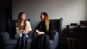 Duas amigas alegres conversam e sorriem, sentando-se em cadeiras cinzentas no café à moda na noite do inverno video estoque