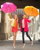 Duas amigas alegres que saltam com guarda-chuvas Imagem de Stock Royalty Free