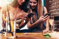 Duas amigas alegres que usam o telefone que olha a tela que sorri ao comer o café da manhã na casa do café fotografia de stock