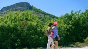 Duas amigas andam ao longo do trajeto e escalam acima o platô da montanha vídeos de arquivo