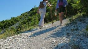 Duas amigas andam ao longo do trajeto e escalam acima o platô da montanha filme