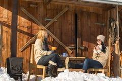 Duas amigas apreciam a casa de campo da neve do inverno do chá Fotografia de Stock