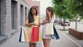 Duas amigas atrativas discutem comprar após a compra 4K vídeos de arquivo