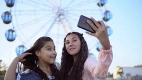 Duas amigas bonitas fazem um selfie no fundo de uma roda de Ferris 4K Close-up filme