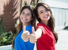 Duas amigas caucasianos que mostram o polegar exterior na cidade Imagens de Stock Royalty Free