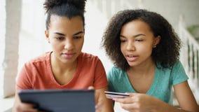 Duas amigas encaracolado alegres da raça misturada que compram em linha com tablet pc e cartão de crédito em casa foto de stock royalty free