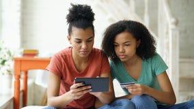 Duas amigas encaracolado alegres da raça misturada que compram em linha com tablet pc e cartão de crédito em casa foto de stock