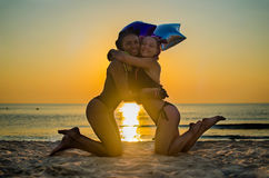 Duas amigas estão abraçando na praia Imagens de Stock