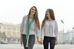 Duas amigas estão andando através da cidade, guardando as mãos e Fotografia de Stock Royalty Free
