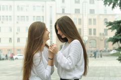 Duas amigas estão guardando as mãos e estão apreciando a reunião Fotografia de Stock